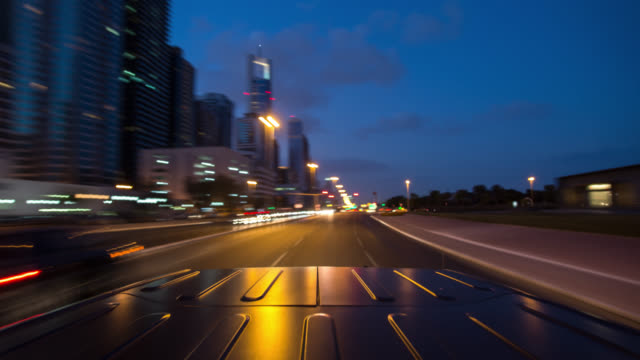 vidéos et rushes de black off road car driving through dubai city during dawn. roof of the car in foreground. streaking reflections in the car's roof and background. - tout terrain urbain