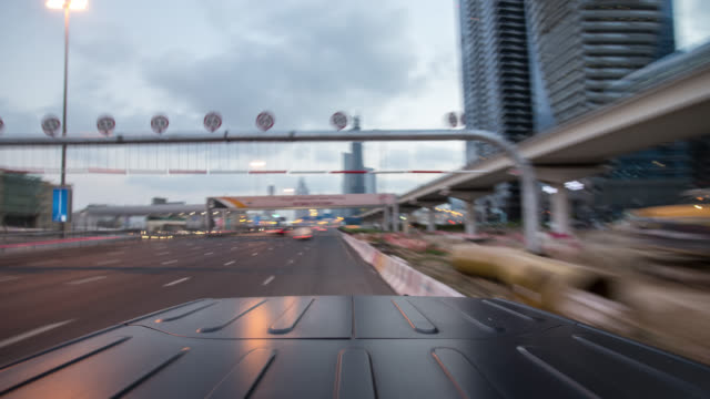 vidéos et rushes de black off road car driving through dubai city during early morning. roof of the car in foreground. streaking reflections in the car's roof and background. - tout terrain urbain