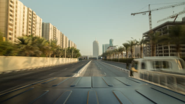 Black off road car driving through Dubai city during early sunlight. Roof of the car in foreground.