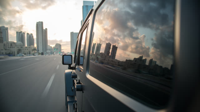 vidéos et rushes de black off road car driving through dubai city with the side of the car in foreground. streaking reflections in the car's surface and window, city background. - tout terrain urbain