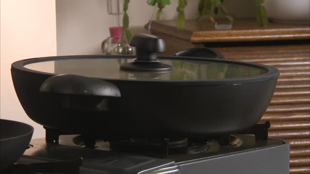 vídeos de stock, filmes e b-roll de black pan with a lid - espátula