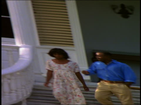 vidéos et rushes de distorted 3 black people (1 male) walking up + down steps of mansion / jamaica - homme dans un groupe de femmes