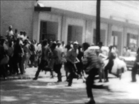 Black protesters running across street by police at civil rights demonstration / Alabama