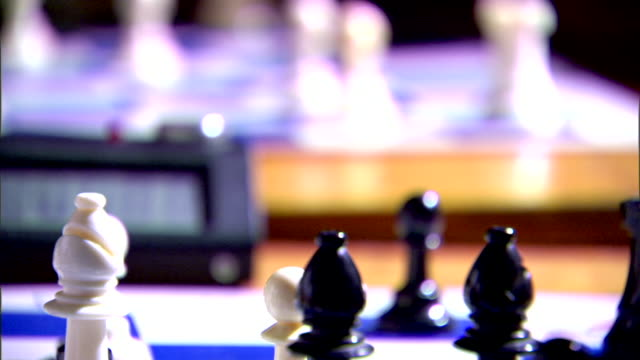 Black queen standing on board black male fingers moving pawn PAN to white side of board male hand placing bishops off board