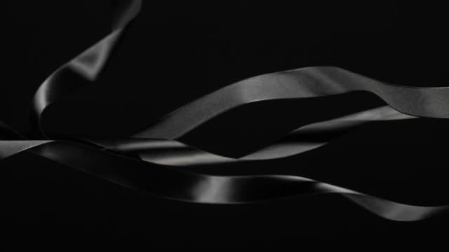 black ribbons on black background, for celebration events and party for new year, birthday party, christmas or any holidays, waiving and curling in super slow motion and close up - loopable moving image stock videos & royalty-free footage