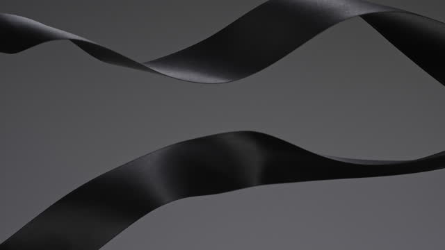 black ribbons on grey background, for celebration events and party for new year, birthday party, christmas or any holidays, waiving and curling in super slow motion and close up - anniversary stock videos & royalty-free footage