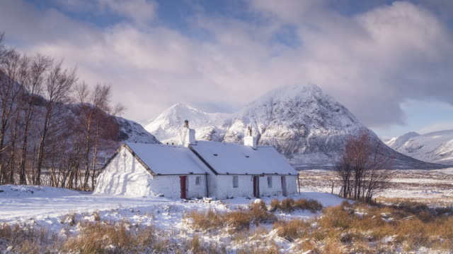 Black Rock Cottage with Buachaille Etive Mor in distance on snow covered Rannoch Moor, Scotland, UK.