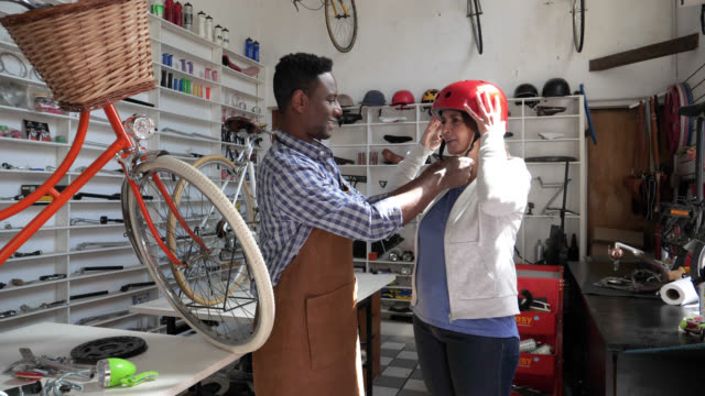 Black salesman at a bicycle shop suggesting a helmet for a female customer both talking and smiling