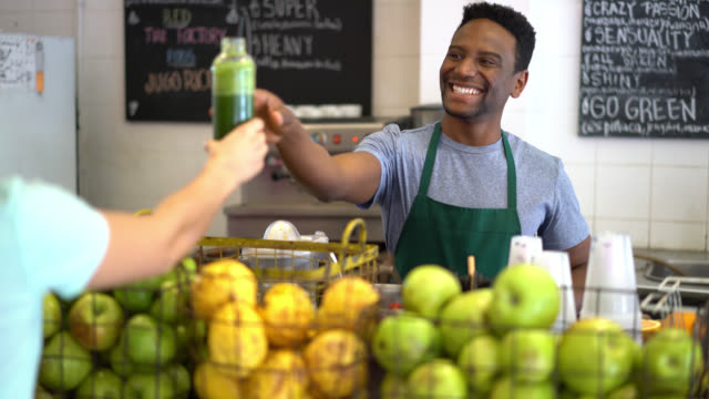 Black salesman working at a juice bar passing a green juice to an unrecognizable customer looking very happy and smiling