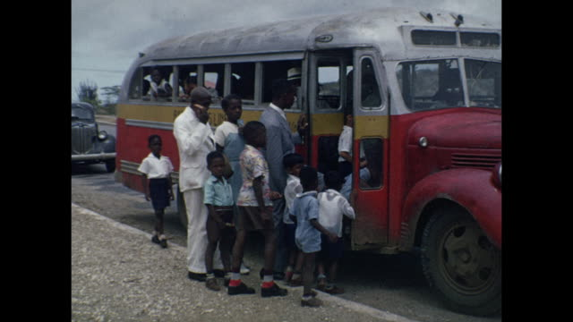 1954 HOME MOVIE Black schoolchildren getting on bus / Aruba, Lesser Antilles