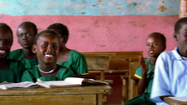 MS PAN Black schoolchildren smiling + clapping at desks in classroom / Kenya