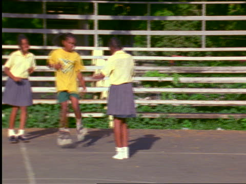 pan 3 black schoolgirls playing double-dutch jump rope in playground / st. john, virgin islands - skipping stock videos & royalty-free footage