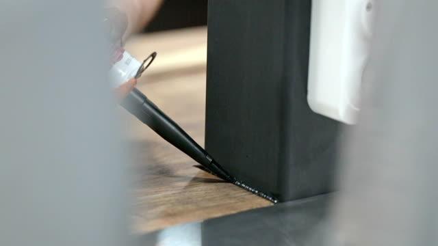 il sigillante nero viene applicato alla cucitura tra il tavolo e la colonna. - sigillante video stock e b–roll