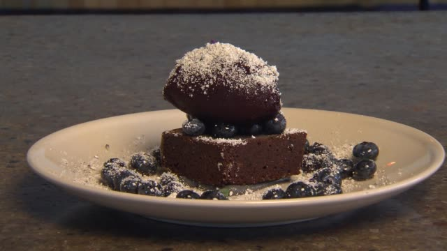 black sesame cake with blueberries on a plate of wine at parachute restaurant in chicago on oct 10 2014 - sesame stock videos and b-roll footage