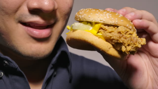 black shirt men are eating chicken burgers - black shirt stock videos & royalty-free footage
