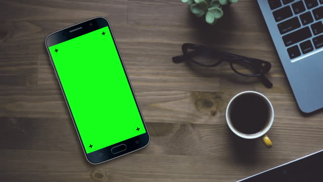 black smartphone on desk with chroma key green screen - desk stock videos & royalty-free footage