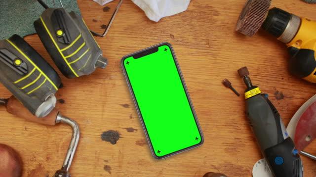 Schwarz Smartphone auf Werkbank mit Chroma-Key-Green-Screen