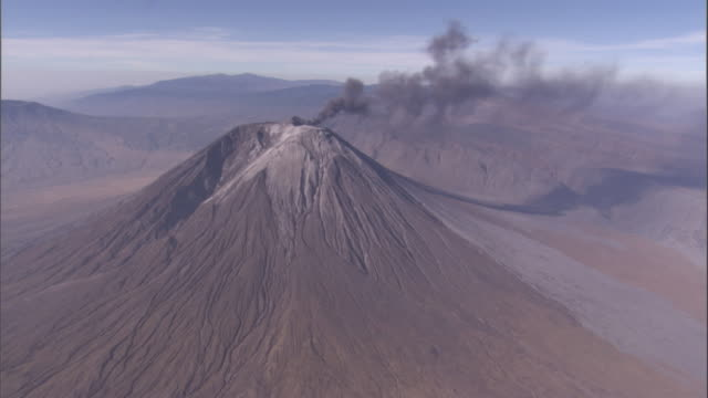 black smoke billows from the oldoinyo lengai volcano. available in hd. - vulkanausbruch stock-videos und b-roll-filmmaterial