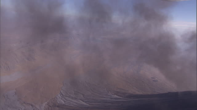 Black smoke drifts across the sky from the Oldoinyo Lengai volcano. Available in HD.