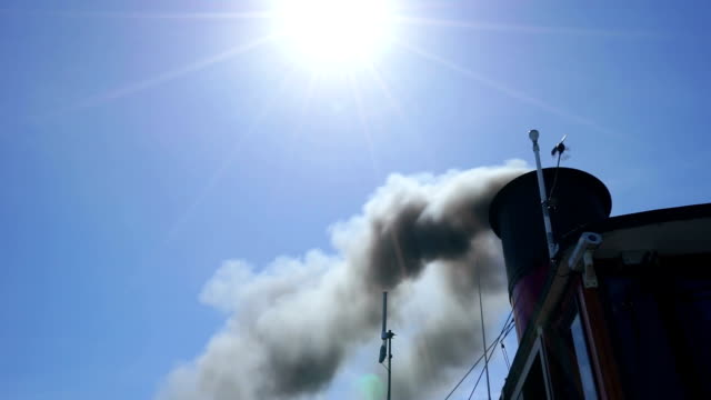 black smoke from chimney in blue sky