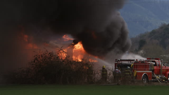 black smoke rolls above a house on fire as firefighters aim streams of water from a hose truck - myrtle creek stock videos and b-roll footage