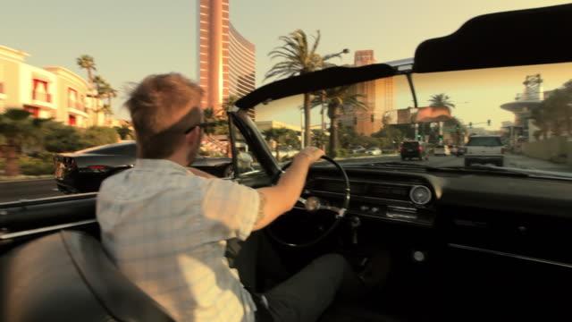 A black sports car passes a convertible on the Las Vegas Strip.