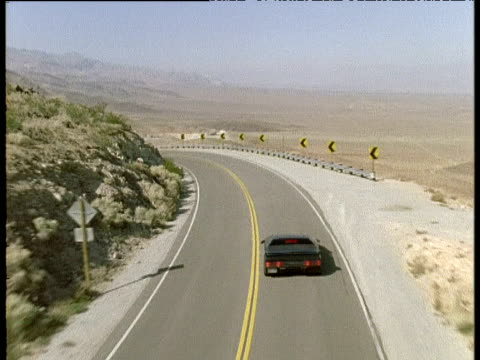 Black sports car turns corner on mountain road, USA
