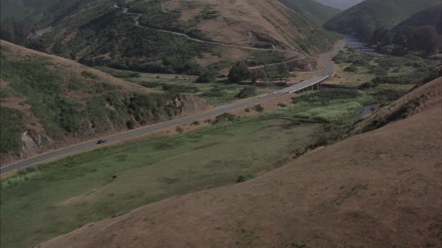 A black station wagon  traveling down a two-lane highway toward a lake.