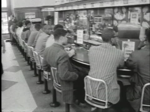black students conduct a sit-in at a lunch counter, hoping to be served. - アメリカ公民権運動点の映像素材/bロール