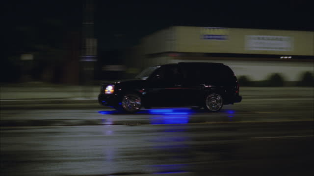 stockvideo's en b-roll-footage met ws pan black suv cadillac escalade on wet city street at night - sports utility vehicle
