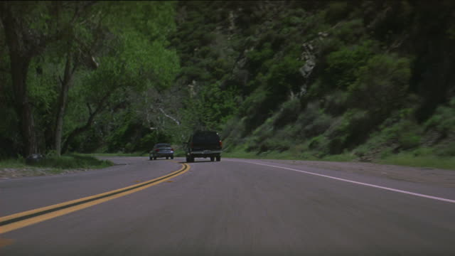 A black SUV chases a sedan and bumps it in the back as the two cars drive down a mountain highway.