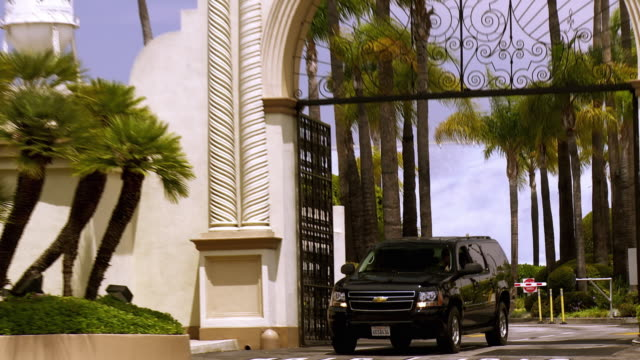 ws zo black suv exiting main gate at paramount studios and turning onto melrose avenue / hollywood, california, usa  - sports utility vehicle stock-videos und b-roll-filmmaterial