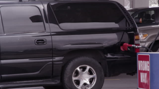 black suv fueling as minivan pulls in. - people carrier stock videos & royalty-free footage
