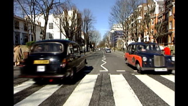 "black taxi cabs along over pedestrian crossing that featured on beatles ""abbey road"" album - itv london tonight weekend stock videos & royalty-free footage"