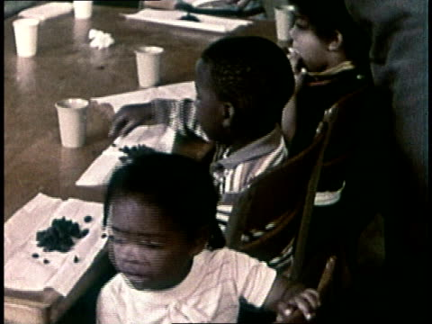 black teacher dishing out candy raisins to students / students sitting at table / teacher handing out cups / teacher pouring milk into boy's cup - 1972 stock videos and b-roll footage