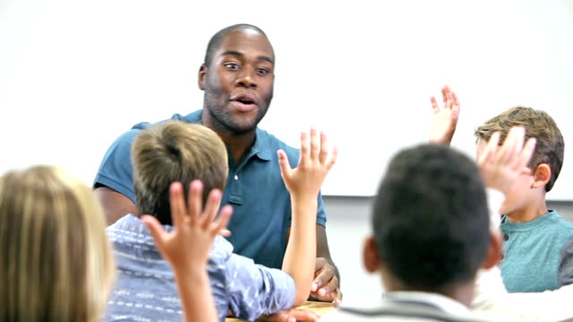 Black teacher talking to elementary school students