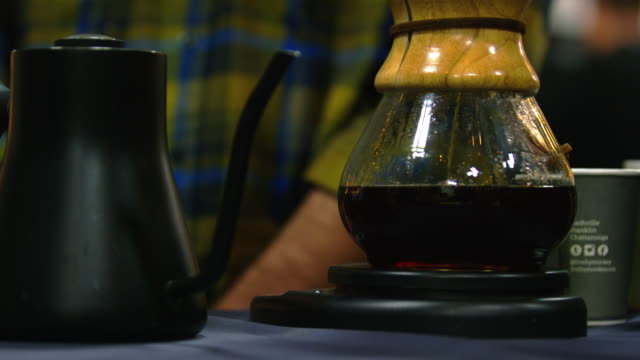 a black teakettle with a spout sits next to a glass pour-over coffee maker as the coffee filters down the sides and fills the reservoir at the bottom while a barista works in the background in a coffee shop - pour spout stock videos & royalty-free footage