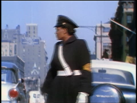 1957 Black traffic policewoman on street signaling with hands + looking at camera