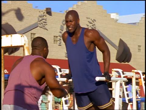 black trainer encouraging black man doing dips on machine at muscle beach / venice beach, ca - ベニスビーチ点の映像素材/bロール