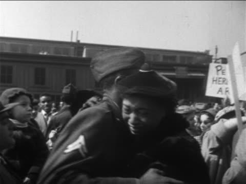 black us soldier hugging woman in midst of welcome crowd / end of korean war / newsreel - militäruniform stock-videos und b-roll-filmmaterial