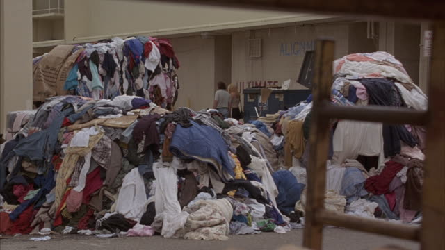 a black van crashes through a pile of clothes in an alley. - 服装点の映像素材/bロール