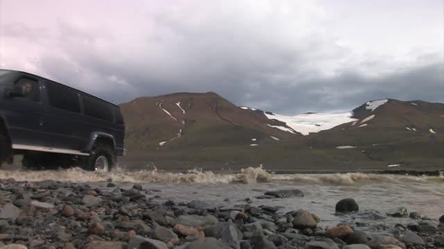 vídeos de stock e filmes b-roll de black van fording a river. - carro 4x4