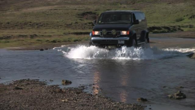 vídeos de stock, filmes e b-roll de black van fording a river. - islândia central