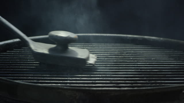 a black wire brush cleans the metal grate of an outdoor barbecue grill - grilled stock videos and b-roll footage