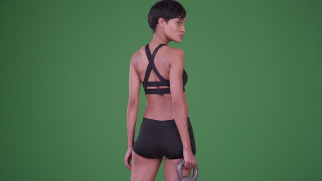 black woman athlete holding kettle bell weight on green screen - 人の背中点の映像素材/bロール
