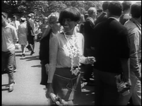 vidéos et rushes de black woman caucasian woman in miniskirts walking past camera at bein / london - 1967