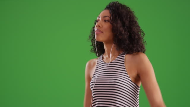 vídeos de stock, filmes e b-roll de black woman dancing while listening to music app on smartphone with greenscreen - mulheres