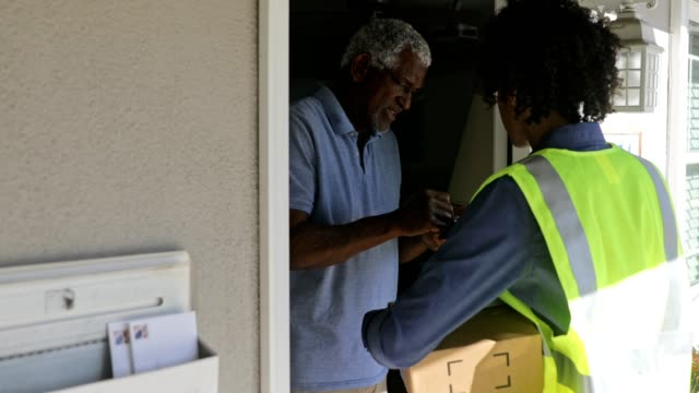 black woman delivers package to customer - postal worker stock videos & royalty-free footage