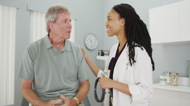 black woman doctor being positive with senior man - listening to heartbeat stock videos and b-roll footage