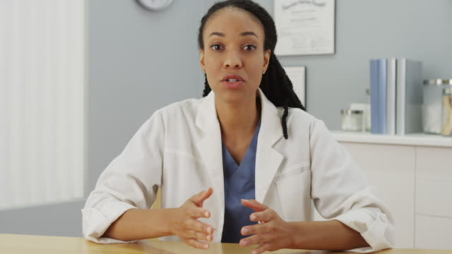 black woman doctor talking to the camera - lab coat stock videos & royalty-free footage